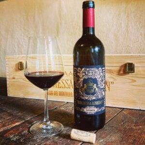 """Vino rosso del Montello """"Grinera IGT Colli Trevigiani"""", versato in un calice da degustazione. Sullo sfondo, la confezione in legno firmata Cantina Barchesa Loredan."""